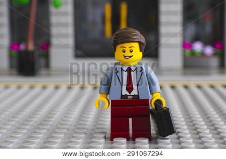 Tambov, Russian Federation - June 22, 2017 Lego Businessman With Suitcase Stay On Lego Gray Baseplat