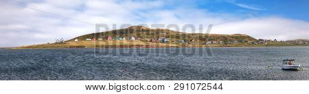The colorful houses of  Havre Aubert, iles de la Madeleine, or the Magdalen Islands, Canada. Panorama of the coastine with houses, small boat and the Gulf of St Lawrence