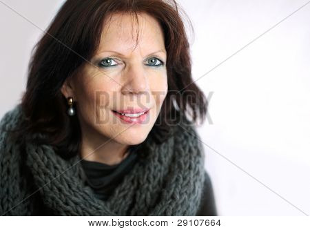 Mature woman portrait with a loop scarf on bright background