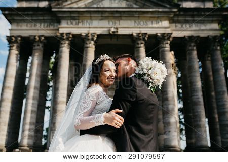 Amazing Portrait Of A Wedding Couple Which Is Standing Near The Old Renaissance Palace. They Are Emb