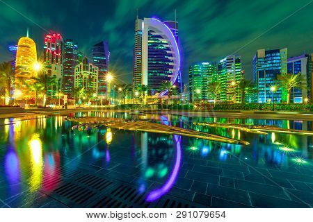Doha West Bay High Rises Illuminated By Night Reflecting In Downtown Park. Colorful Glassed Skyscrap