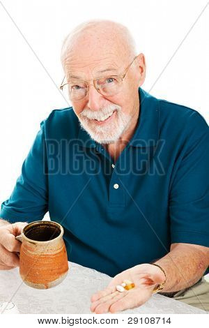 Senior man taking his vitamins, supplements, and/or medicine.  White background.