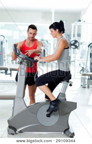woman on stationary bicycle with personal trainer at fitness gym