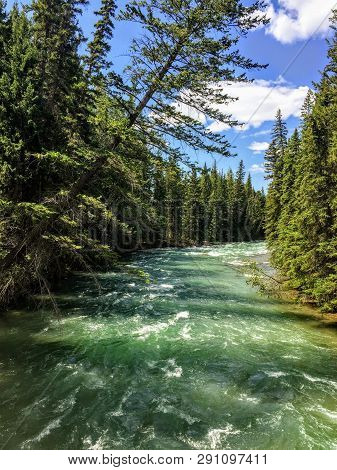 A Closeup View Of The Turquoise Waters Of Athabasca River Surrounded By Evergeen Forest, Along The M