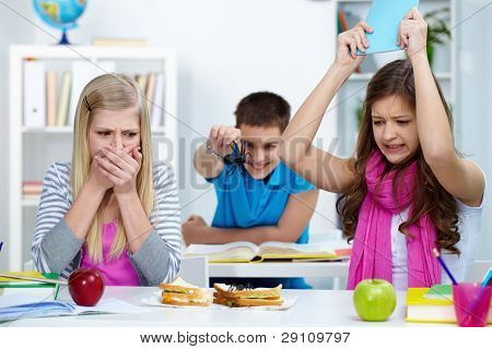 Shocked girl looking at spider on one of their sandwiches while another one going to kill it with copybook