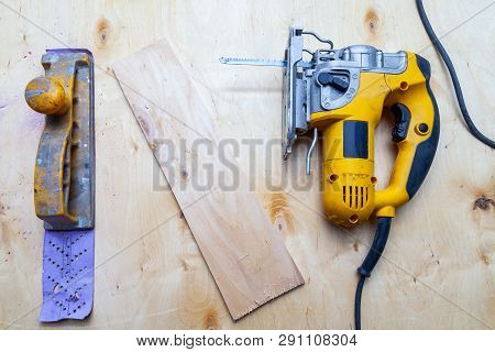 Flat lay of a yellow electric jigsaw and hand plane ready for work use on the workbench with sawn plywood in a workshop for carpentry work. Tool for industry and production. poster