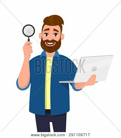 Smart Bearded Young Man Showing/holding Magnifying Glass And Laptop Computer In Hand. Search, Find,