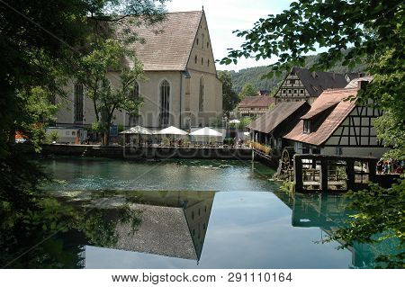 Blautopf, Spring Of River Blau In Blaubeuren, Southern Germany, With Monastery Church And Historic H