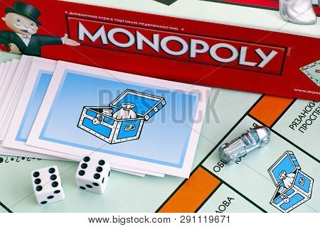 Tambov, Russian Federation - January 26, 2018 Monopoly Board Game Box, Community Chest Cards, Tokens