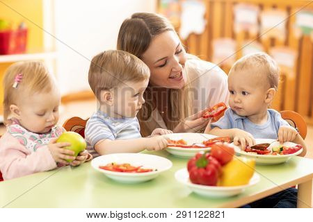 Babysitter Feeding Nursery Babies. Toddlers Eat Healthy Food In Daycare Center