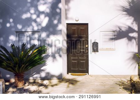 White Mediterranean House With Brown Door , Close Windows And Frontage.