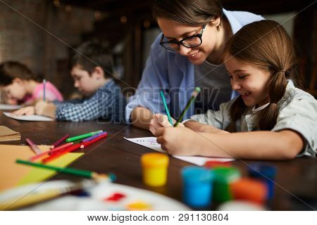 Portrait Of Smiling Young Woman Working With Kids Drawing In Art Class, Copy Space