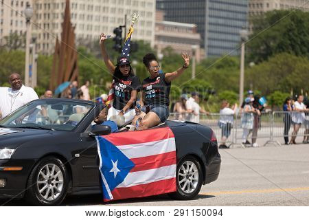 Chicago, Illinois, Usa - June 16, 2018: The Puerto Rican Day Parade, Two Women On A Car Waving At Sp