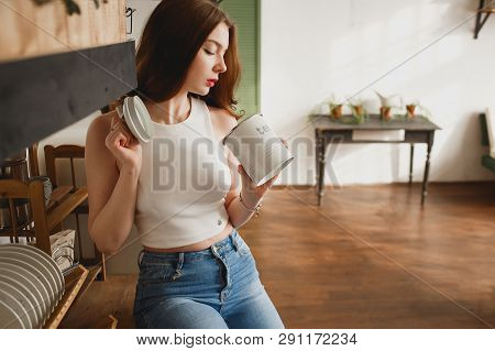 Young sensual girl in the kitchen provocatively looking into an open can of tea poster