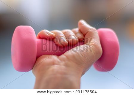 A Woman  Trains With Pink Dumb Bells