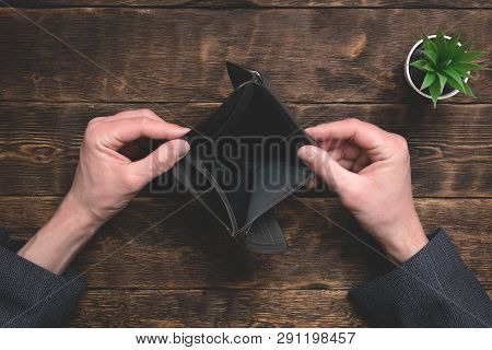 Empty wallet in hands on an office table background. No money concept. Debts. Bankruptcy. poster