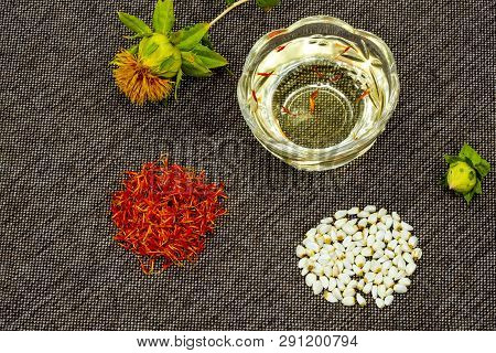 Safflower. Oil, Seeds, Bud, Flower, Red Inflorescences Of Wild Saffron. Close-up, Gray Fabric Backgr