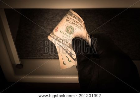 The Hand Of A Man In A Black Glove Holds Us Dollar Bills. Open Metal Safe. The Concept Of Saving Mon
