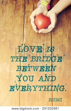 Famous Persian Poet Rumi Quote About Love Is Bridge Printed Over Image With Red Heart In Hands