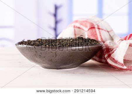Lot Of Pieces Of Dry Black Tea Earl Grey In A Grey Ceramic Bowl With A Tea Towel With Blue Window In