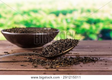 Lot Of Pieces Of Dry Black Tea Earl Grey In A Grey Ceramic Bowl With Silver Spoon Green Tea Field Be