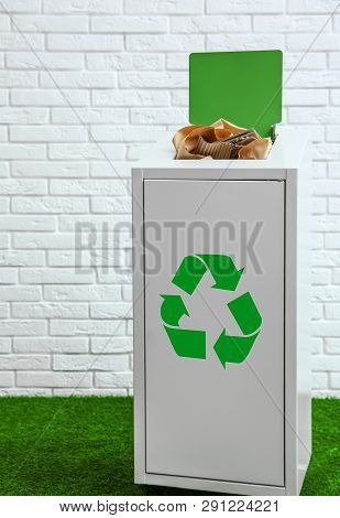 Overfilled Trash Bin Near Brick Wall Indoors. Recycling Concept