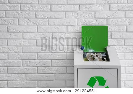 Overfilled Trash Bin With Recycling Symbol Near Brick Wall. Space For Text