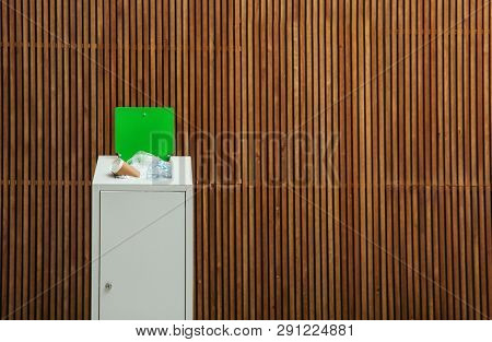 Overfilled Trash Bin Near Wooden Wall, Space For Text. Recycling Concept
