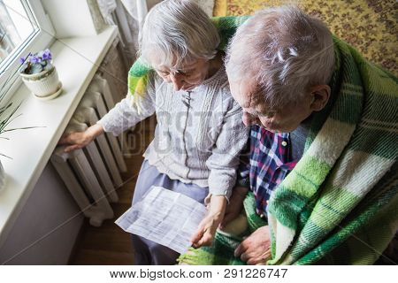 The Senior Woman Holding Gas Bill In Front Of Heating Radiator. Payment For Heating In Winter.