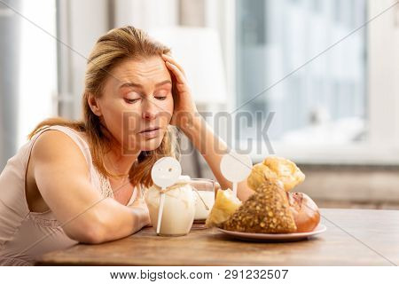 Housewife Sitting At The Table And Looking At Foods Evoking Allergies
