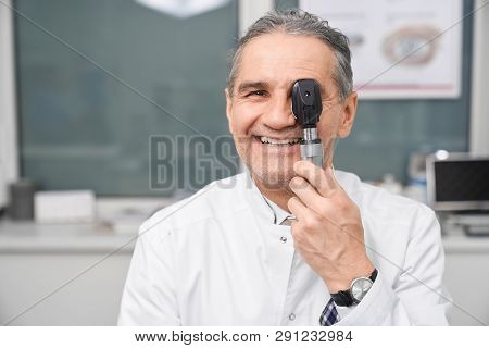 Doctor Optometrist Posing With Special Eye Equipment In Medical Clinic. Mature Medical Worker In Whi