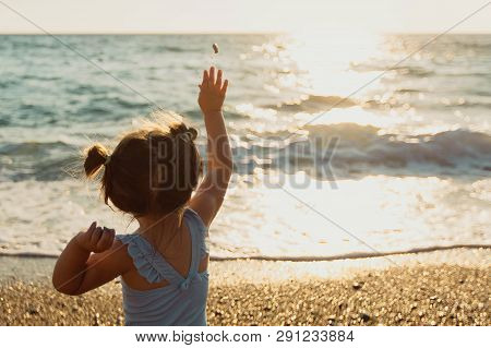 A Little Girl In A Blue Sweamsuit Sits With Her Back Against The Sea And Throws Stones At The Waves.