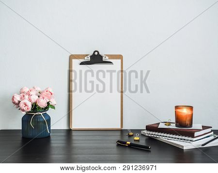 Clipboard With White Empty Page On Table. Clipboard, Pink Flowers, Scented Candle, Stack Of Books On