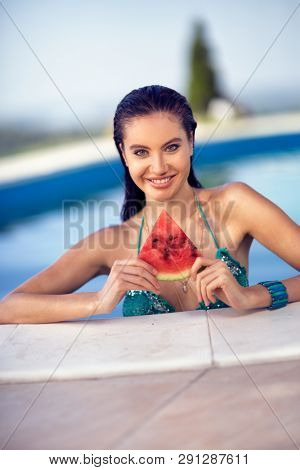 sexy woman with dark hair eating watermelon while standing in swimming pool