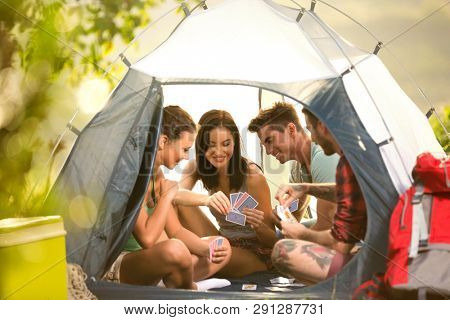 Group of young people on camping trip in countryside sitting in tent and playing cards