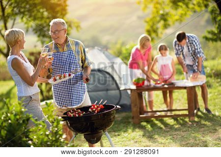 grandparents drinking  wine and making barbeque for family