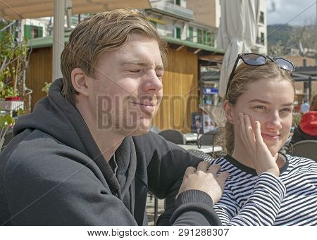 Young Handsome Couple Sit In Cafe And Squint In Stark Sunshine