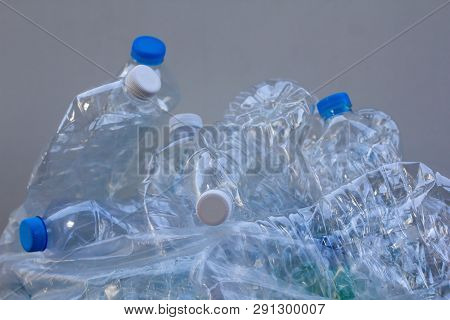 Clear And Green Recyclable Plastic Bottle In Paper Garbage Bin For Recycling. Waste Management And P