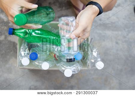 Hand  Holding Clear And Green Recyclable Plastic Bottle Putting In Paper Garbage Bin For Recycling.