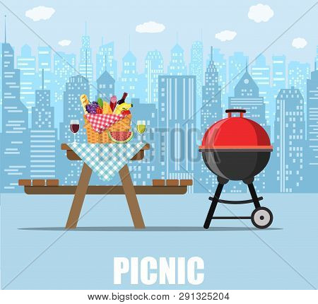 Summer Picnic Table On City Background. Bbq Grill, Straw Basket And Food For Outing On Public Park.