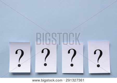 Four Printed Question Marks On White Paper Forming A Lower Border On A Blue Background Neatly Laid I