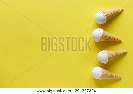 Side Border Of Frozen Ice Cream Cones With Scoops Of Creamy Vanilla Dessert On A Cool Toned Yellow B