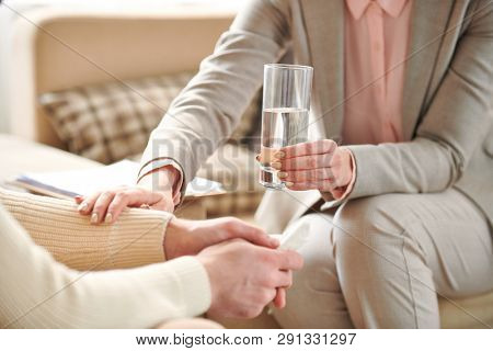 Young woman holding glass of water and keeping hand on man arm while expressing empathy during individual session