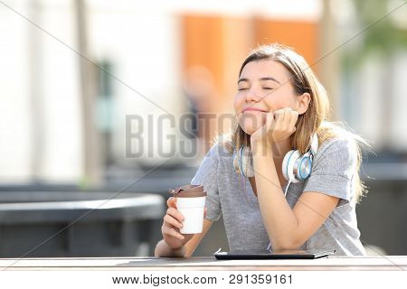 Happy Girl Resting Holding Coffee Cup Sitting In A Park