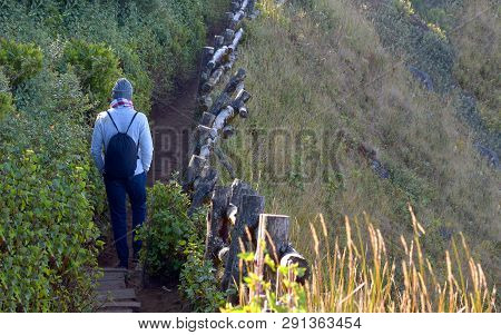 Traveler traveling on footpath beside a cliff, ecotourism in beautiful nature environment in trail on mountain, traveler traveling on trail on mountain, tourist tour in ecotourism, trekking tourist poster