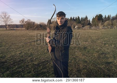 Smiling Young Man Holding A Bow And Arrow