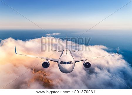 Airplane Is Flying Over Clouds At Sunset In Summer. Landscape With Passenger  Airplane, Low Clouds,