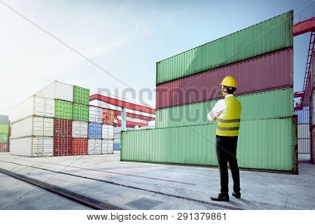 Rear View Of Asian Male Worker With Safety Vest, Hard Hat And Protective Mask Standing On The Dock A