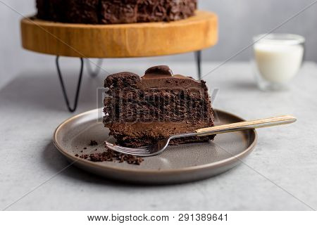 Tasty Piece Of Chocolate Cake On Gray Plate With Fork, With Whole Cocoa Cake On Wooden Stand, Glass