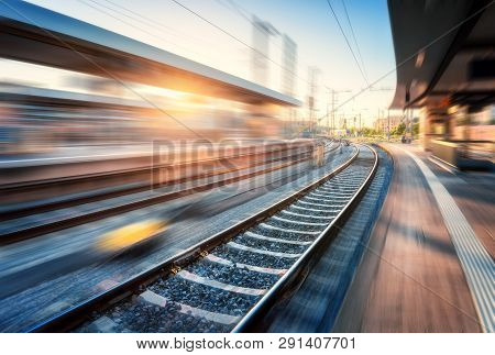 Railway Station With Motion Blur Effect At Sunset. Industrial Landscape With Railroad, Blurred Railw